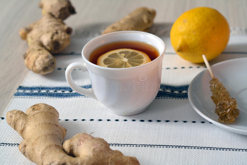 Natural medicine conceipt: ginger lemon tea. In a white cup on embroided towel royalty free stock photos