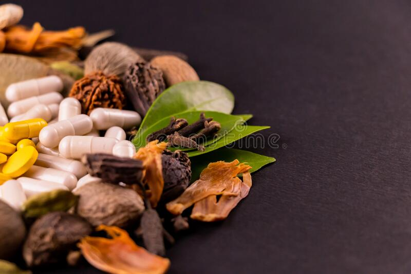 Natural medicine concept. scattered different spices, herbs and herbal capsules with green leaves on black ground royalty free stock photography