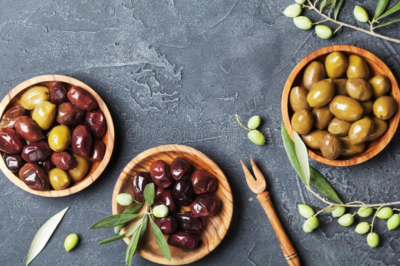 Natural olives in bowls with olive branch on black stone table top view. Natural olives in bowls with olive branch on black stone table from above stock images
