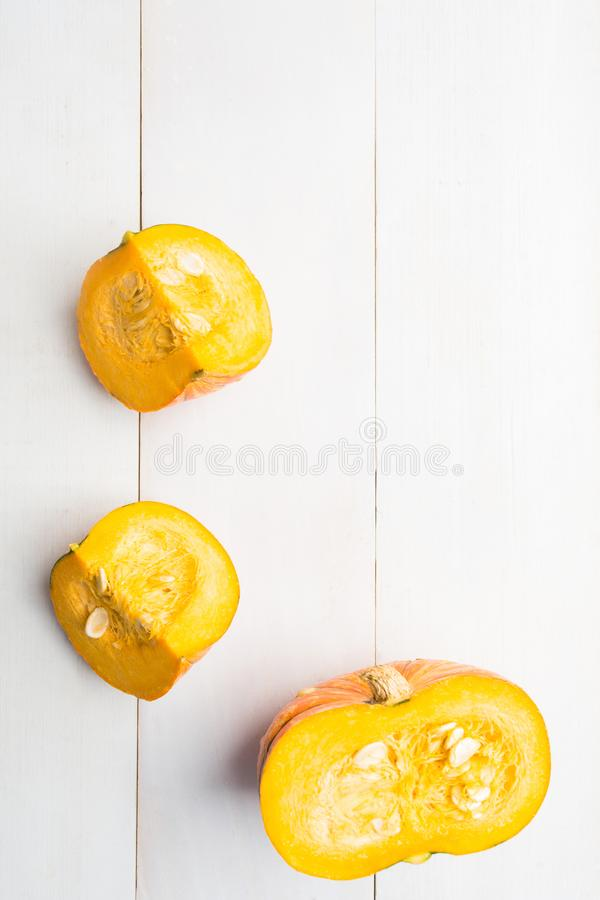 Natural orange cut pumpkin over wooden background with copy space stock images
