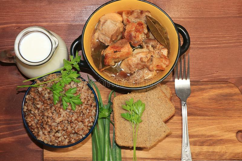 Natural organic buckwheat porridge in a clay pot, meat in a pot, a jug of milk and onions with parsley, top view. stock photo