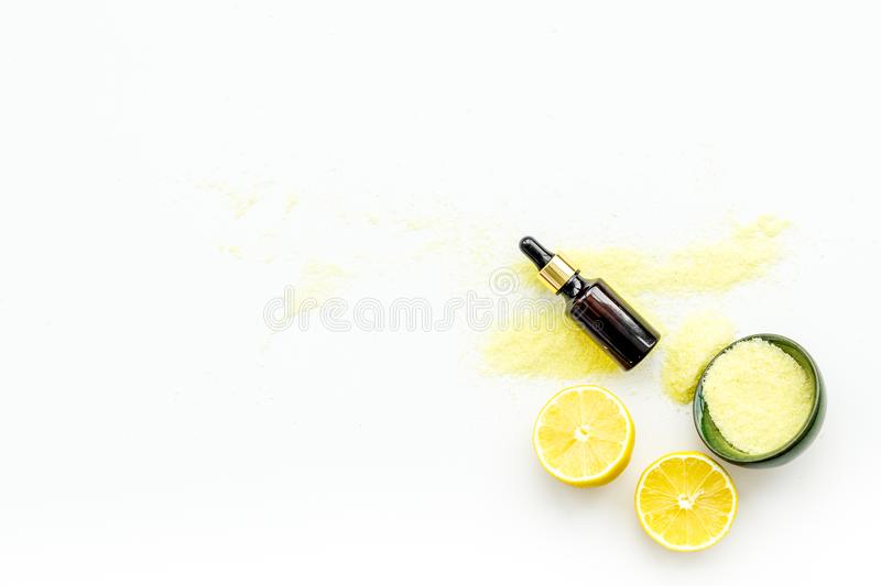 Natural organic cosmetics with lemon. Lemon oil or lotion, spa salt in small bottles on white background top view copy royalty free stock images