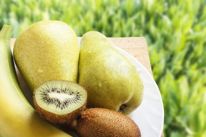 Natural organic fruits on wooden table in nature. Top view on green grasses with copy space. Rustic lifestyle concept.  royalty free stock photo
