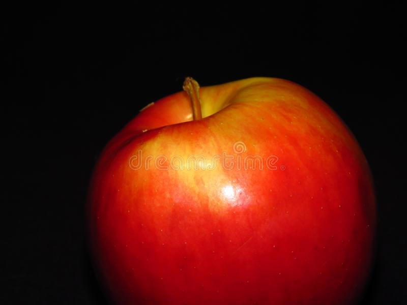 Natural organic healthy fruit. Close up of a ripe red juicy apple on black background. stock photo