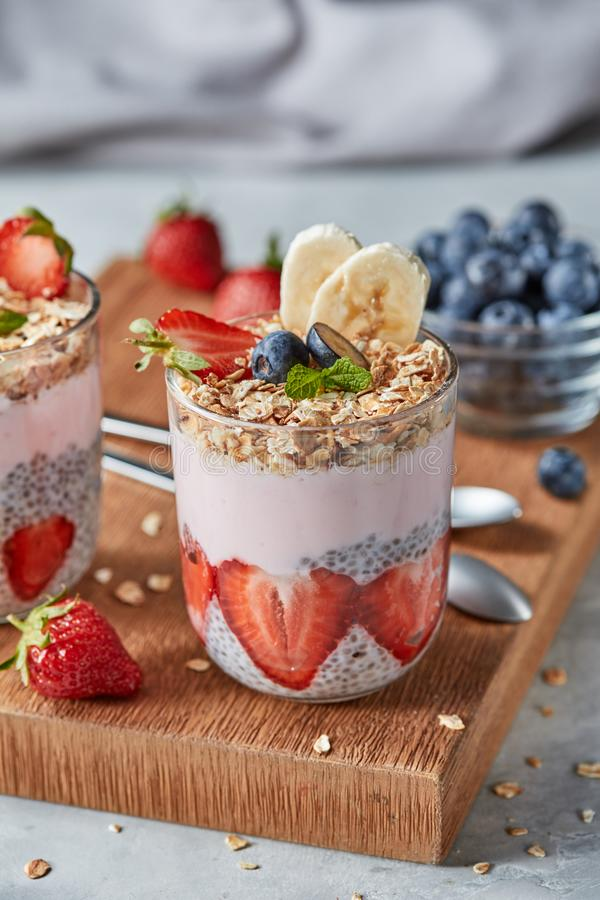 Dietary natural breakfast with fresh organic ingredients - berries, granola, banana in a glass on a wooden table stock photography