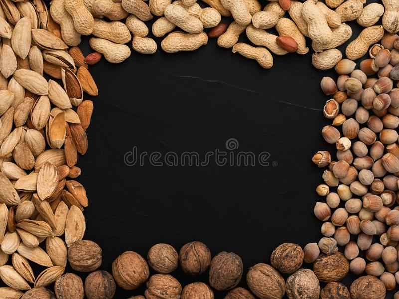 Natural organic nuts, almonds, peanuts, walnuts and hazelnuts on a black background. Top view. The concept of a healthy diet, royalty free stock image