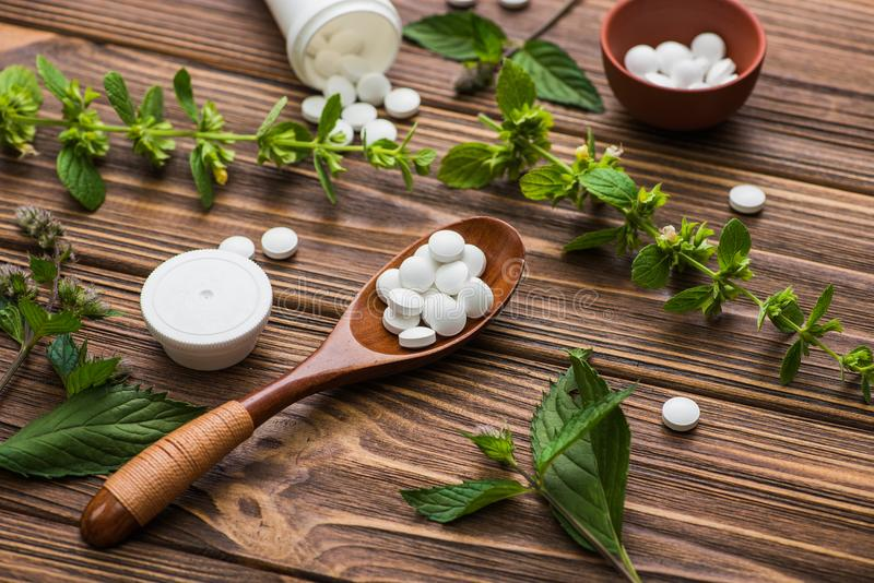 Natural organic pills with herbal plant. On wood table. ethnoscience concept royalty free stock image