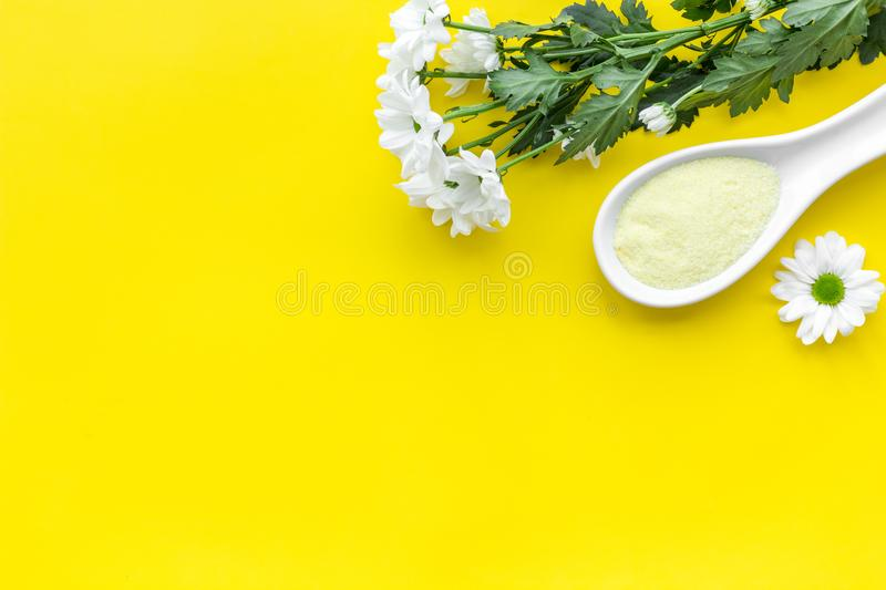 Natural organic spa cosmetics for skin care with chamomile. Spa salt on yellow background top view copy space stock photo