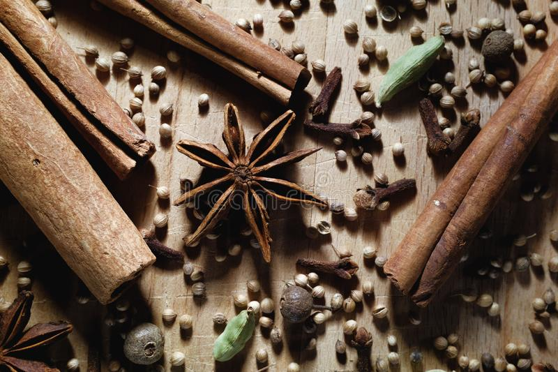 Natural organic spices are scattered on a wooden Board. Texture background with dry aromatic spices star anise, cardamom, black stock photography