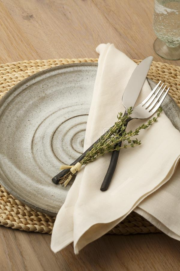 Natural, organic style table setting with wrought iron silverware, handmade plate, cloth napkin and fresh thyme herbs decoration royalty free stock images