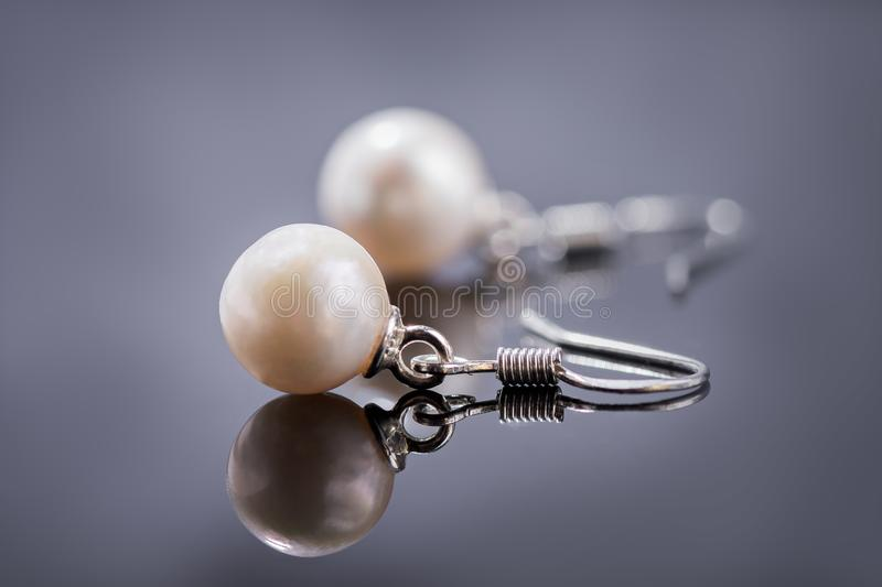 Natural pearl earrings on a dark reflective surface royalty free stock photography