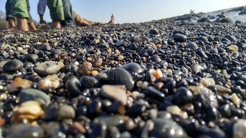 Natural pebbles on ocean shore, royalty free stock images