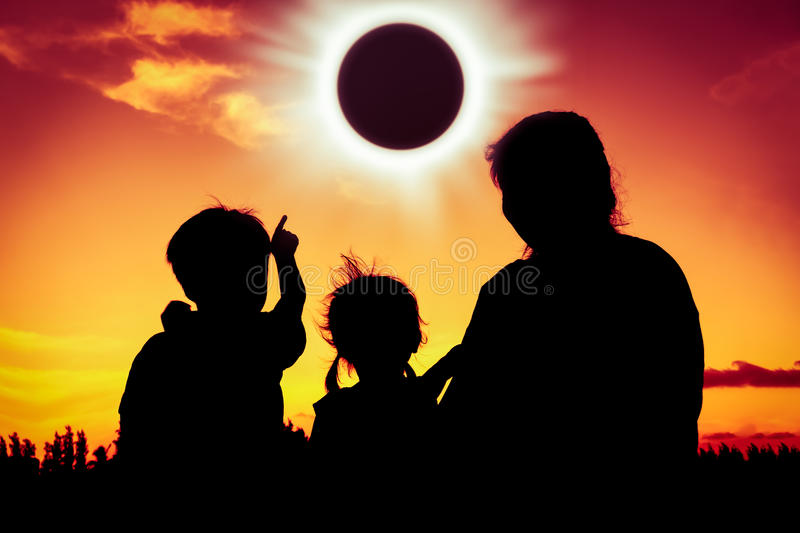 Natural phenomenon. Silhouette back view of family sitting and r. Elaxing together. Boy point to solar eclipse on gold sky background. Happy family spending time stock photo