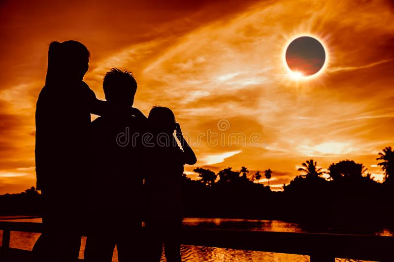 Natural phenomenon. Three person looking at total solar eclipse. royalty free stock image