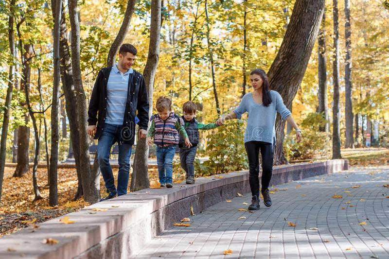 Natural pictures of a happy family of four having fun outsiade on a sunny autumn day. Togetherness and happiness concept stock image