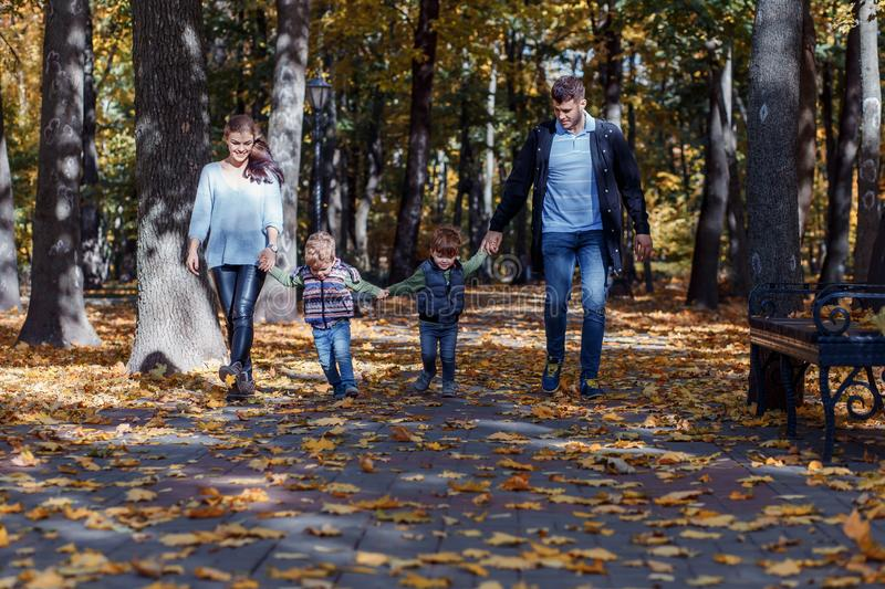 Natural pictures of a happy family of four having fun outsiade on a sunny autumn day. Togetherness and happiness concept royalty free stock photos