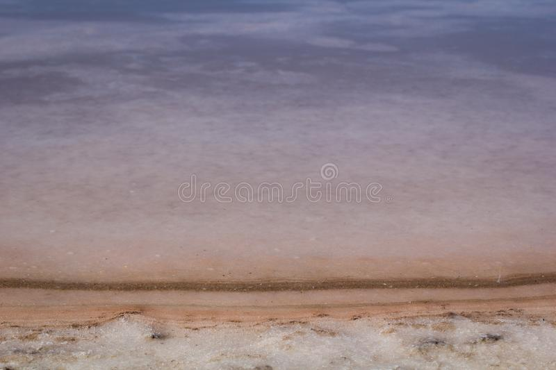 Natural pink salt crystal texture on the sand, macro, close up. Salty lake shore background. Spain, Torrevieja. Edge of the lake royalty free stock photo