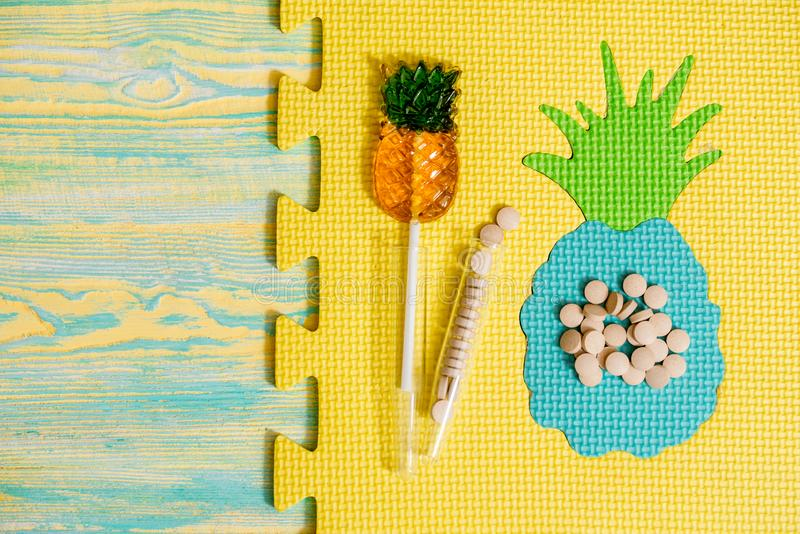 Natural plant-based diet pills, pineapple capsules. Bright pineapple candy on a gray background, crumpled paper. The concept of. Homeopathic medicine. Vitamins stock photos