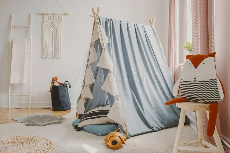 Natural playroom with blue scandinavian tent, wooden ladder, toys and handmade macrame on the wall, real photo royalty free stock photo