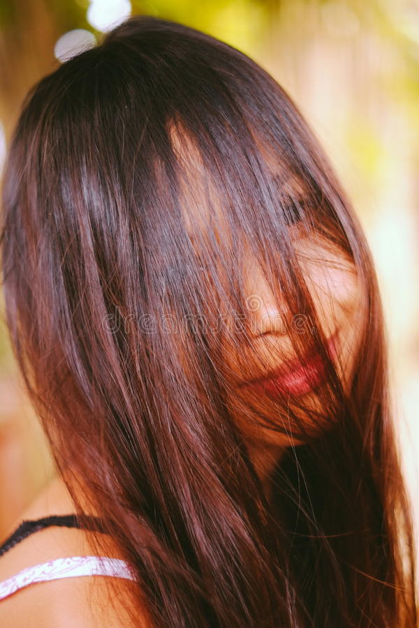 Natural portrait, Asian girl smiling with hair on her face. Native Asian beauty. Local Asian people royalty free stock photo