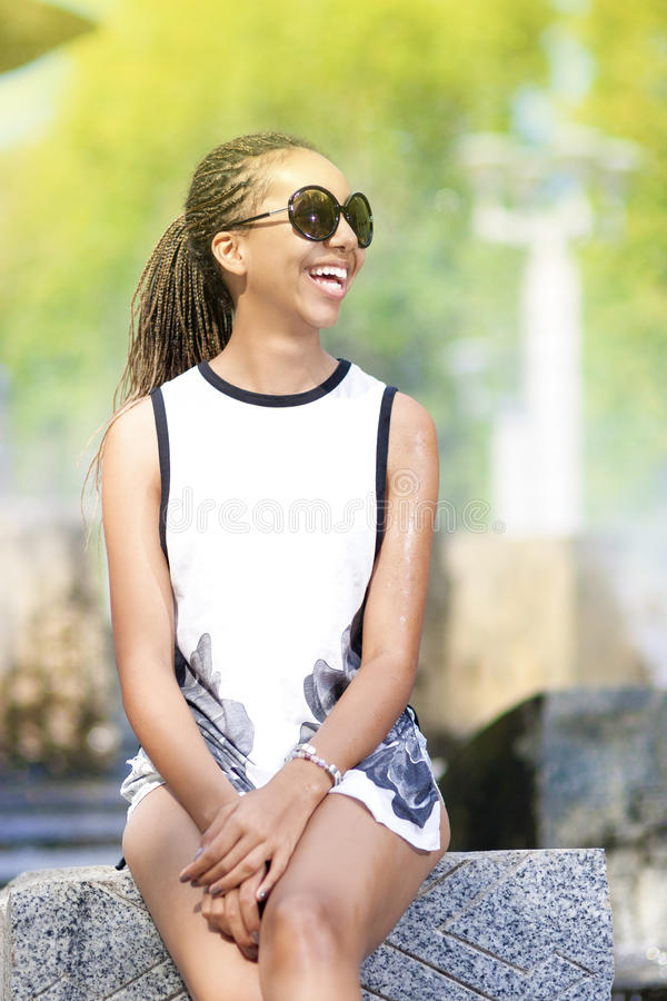 Natural Portrait of Happy Positive African American Teenager Girl With Long Dreadlocks in Sunglasses. In Front of Fountain. Outdoors.Vertical image royalty free stock photos