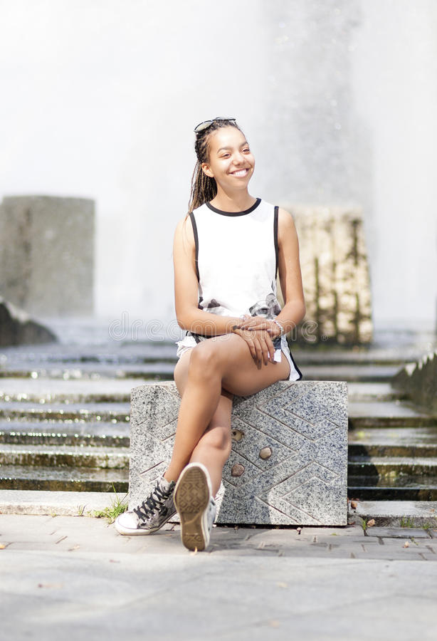 Natural Portrait of Happy Smiling African American Teenager Girl Sitting in Front of Water Fountain. Outside.Vertical Image Orientation royalty free stock photos