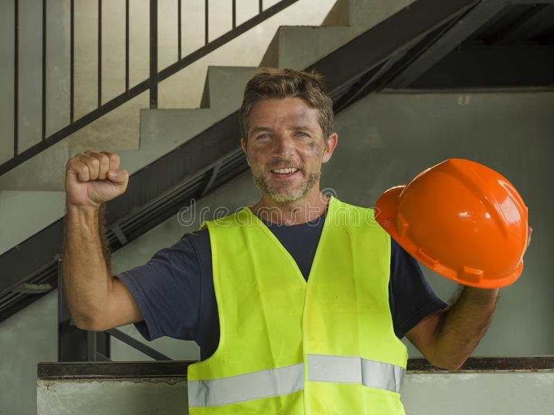 Natural portrait of young attractive and happy builder man or constructor posing cheerful smiling in blue collar job lifestyle and royalty free stock images