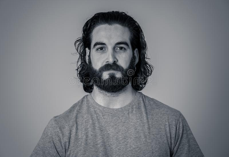 Natural portrait of young attractive man in his 20s looking and posing with neutral face expression. Close up headshot of young Hipster man with natural and stock photo