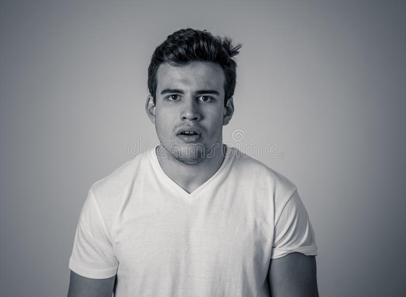 Natural portrait of young attractive man in his 20s looking and posing with neutral face expression. Close up headshot of young latin man with natural and stock photo