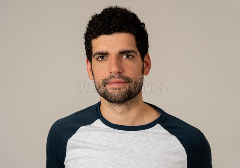 Natural portrait of young attractive man in his 20s looking and posing with neutral face expression. Close up headshot of young latin man with natural and royalty free stock image