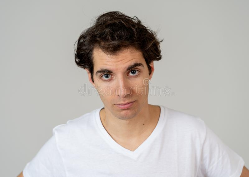 Natural portrait of young attractive man in his 20s looking and posing with neutral face expression. Close up headshot of young latin man with natural and royalty free stock photo
