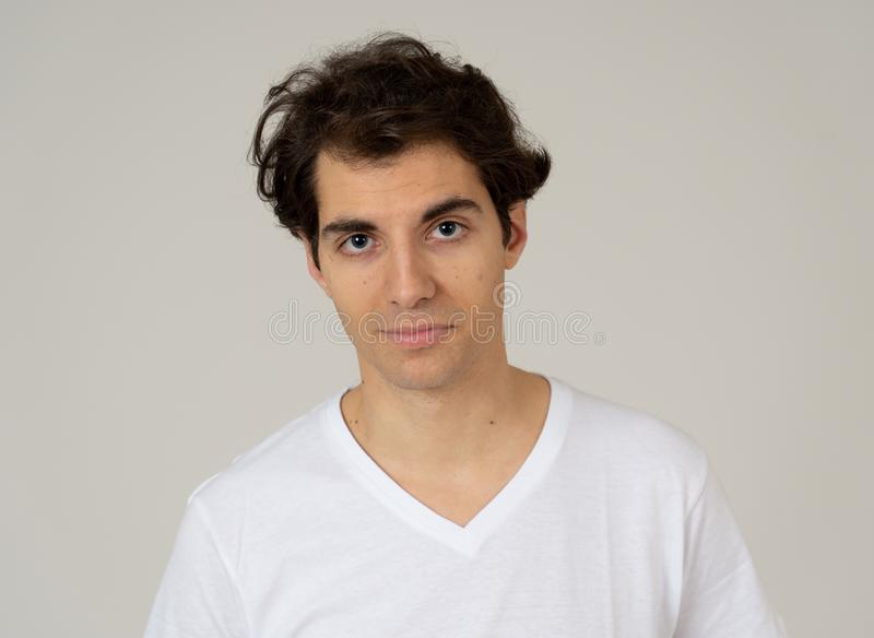Natural portrait of young attractive man in his 20s looking and posing with neutral face expression. Close up headshot of young latin man with natural and stock photos