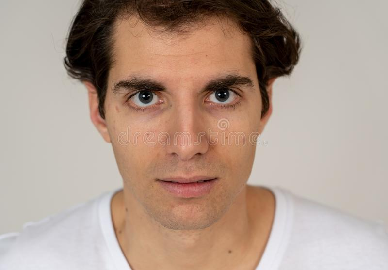 Natural portrait of young attractive man in his 20s looking and posing with neutral face expression. Close up headshot of young latin man with natural and stock images