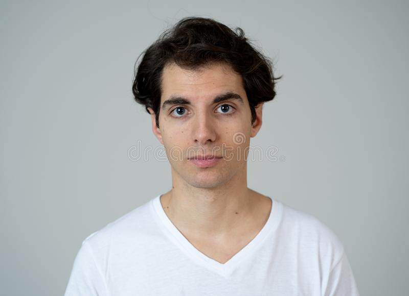 Natural portrait of young attractive man in his 20s looking and posing with neutral face expression. Close up headshot of young latin man with natural and stock image