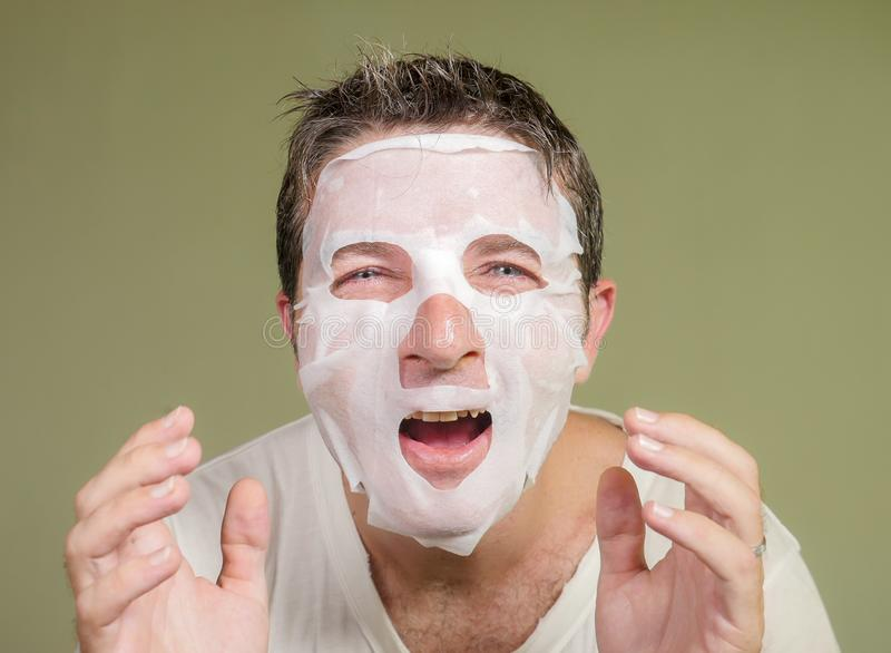 Natural portrait of young happy and funny man applying beauty facial mask looking in the mirror laughing cheerful finding himself royalty free stock photography