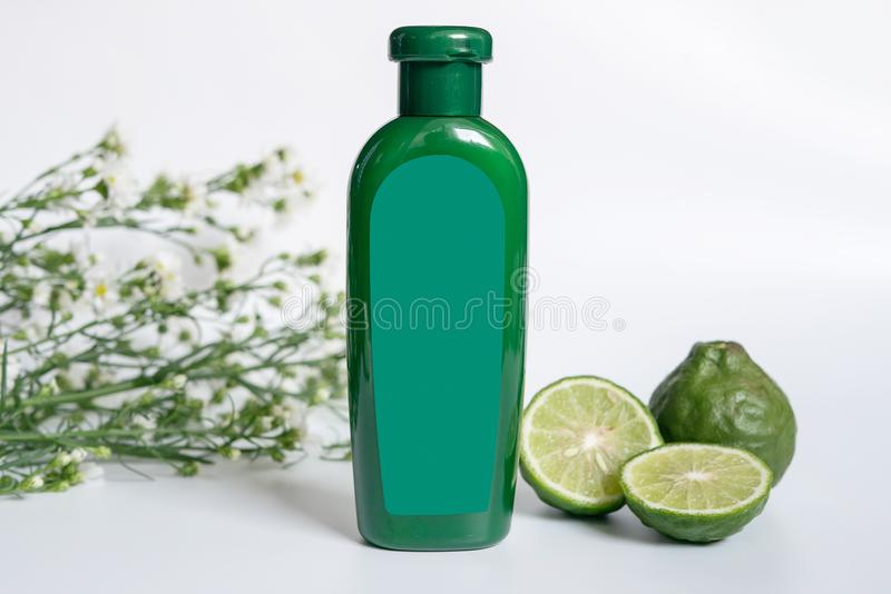 Natural products for hair concept. green plastic bottle with blank label contain herbal bergamot shampoo. Decorate with slide kaffir limes ,kaffir leaf and royalty free stock photos