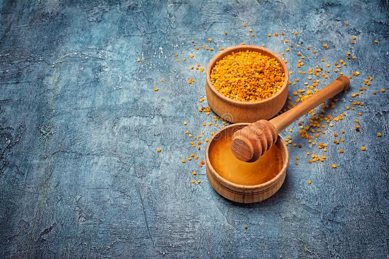 Natural products honey and bee pollen in wooden bowls with honey stick royalty free stock images
