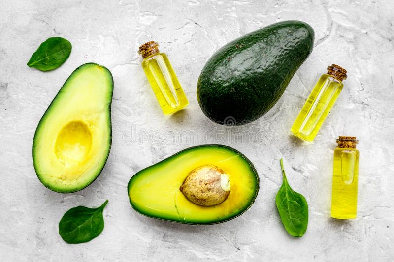 Natural products for skin care. Avocado oil in bottles near sliced avocado on grey background top view close up. Natural products for skin care. Avocado oil in stock photography