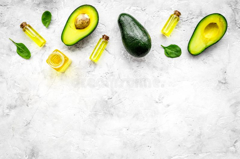 Natural products for skin care. Avocado oil in bottles near sliced avocado on grey background top view copy space. Natural products for skin care. Avocado oil in stock image
