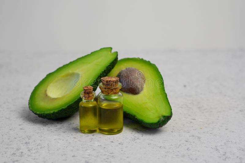 Natural products for skin care. Avocado oil in bottles near sliced avocado on grey background top view copy space.  royalty free stock photos