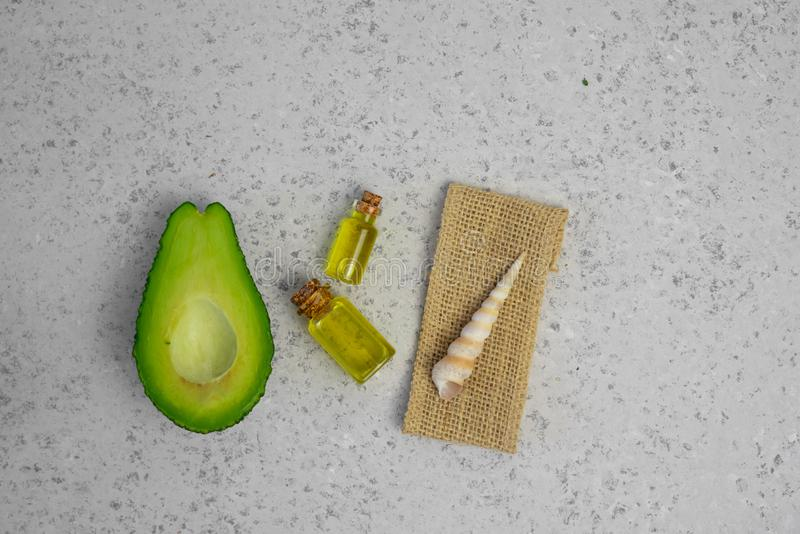 Natural products for skin care. Avocado oil in bottles near sliced avocado on grey background top view copy space.  stock image