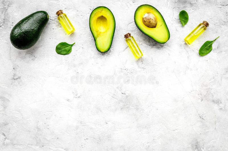 Natural products for skin care. Avocado oil in bottles near sliced avocado on grey background top view copy space. Natural products for skin care. Avocado oil in royalty free stock photography