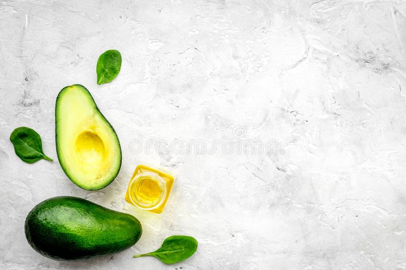 Natural products for skin care. Avocado oil in bottles near sliced avocado on grey background top view copy space. Natural products for skin care. Avocado oil in stock photography