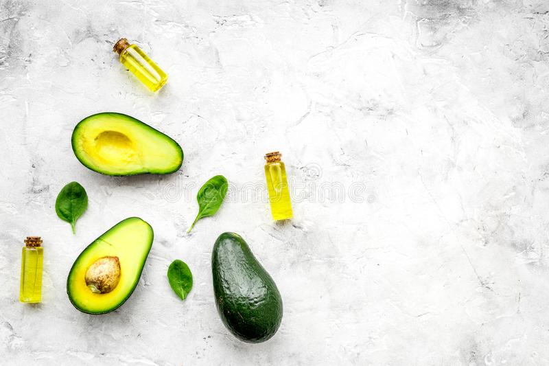 Natural products for skin care. Avocado oil in bottles near sliced avocado on grey background top view copy space. Natural products for skin care. Avocado oil in stock photo