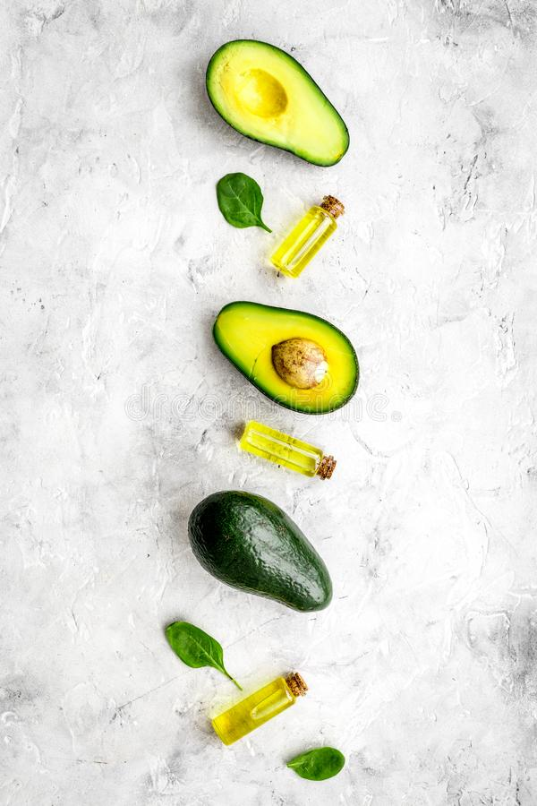 Natural products for skin care. Avocado oil in bottles near sliced avocado on grey background top view copy space. Natural products for skin care. Avocado oil in royalty free stock images