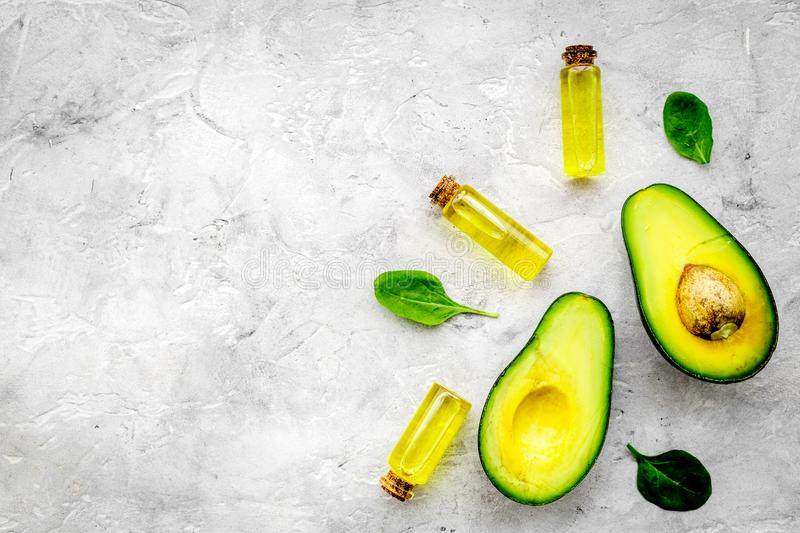 Natural products for skin care. Avocado oil in bottles near sliced avocado on grey background top view copy space. Natural products for skin care. Avocado oil in royalty free stock photos