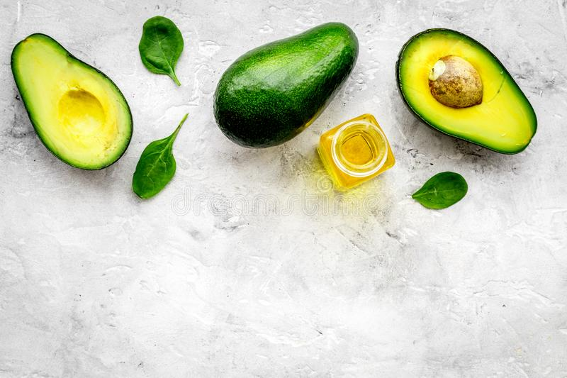 Natural products for skin care. Avocado oil in bottles near sliced avocado on grey background top view copy space. Natural products for skin care. Avocado oil in stock images