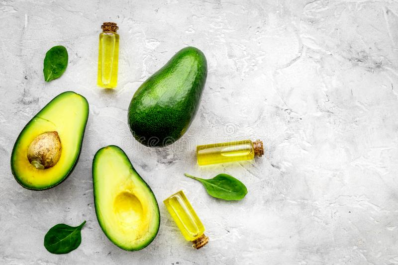 Natural products for skin care. Avocado oil in bottles near sliced avocado on grey background top view copy space. Natural products for skin care. Avocado oil in stock photos