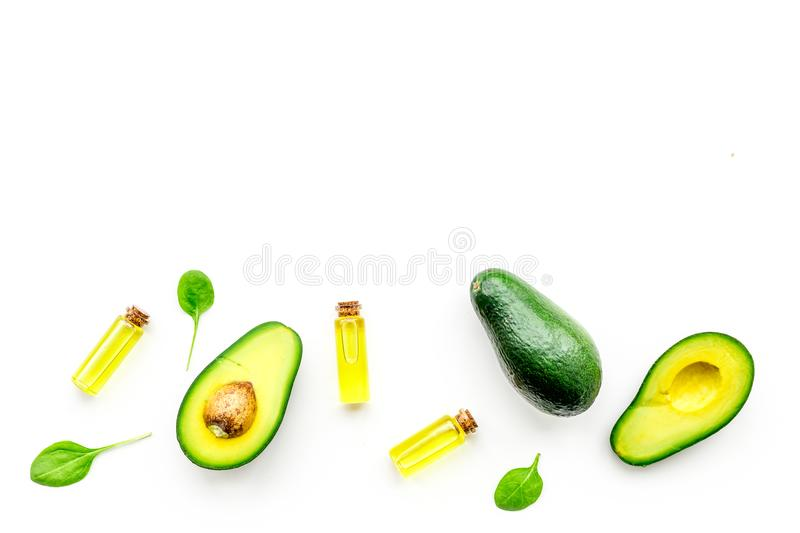 Natural products for skin care. Avocado oil in bottles near sliced avocado on white background top view copy space. Natural products for skin care. Avocado oil royalty free stock photo