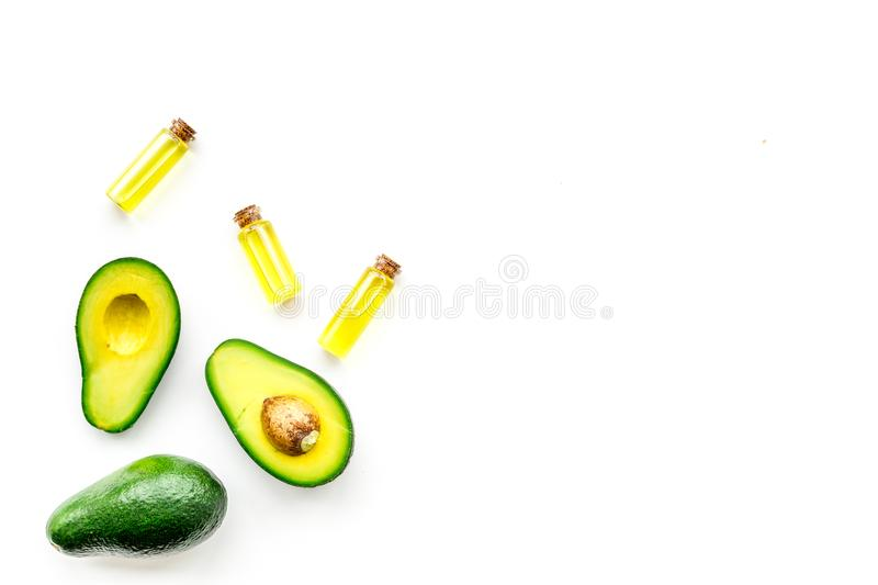 Natural products for skin care. Avocado oil in bottles near sliced avocado on white background top view copy space. Natural products for skin care. Avocado oil stock images